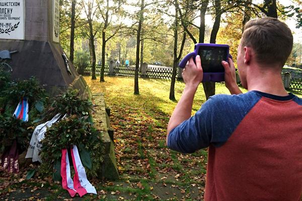 Ein Schüler des Berufskollegs Schloß Neuhaus filmt auf dem Sowjetischen Ehrenfriedhof in Schloß Holte-Stukenbrock mit einem iPad.
