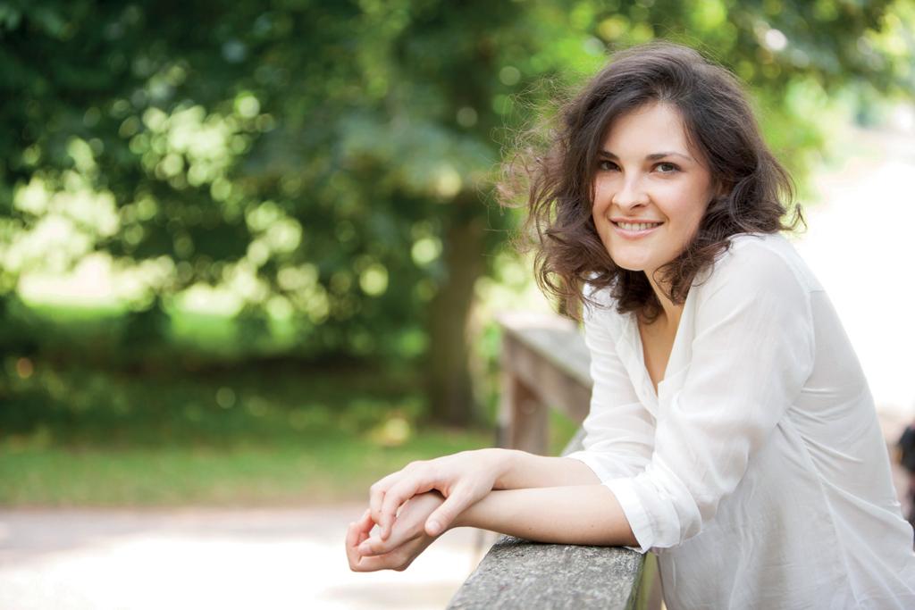Sandra Urba angelehnt an ein Geländer, im Hintergrund das Grün der Natur.