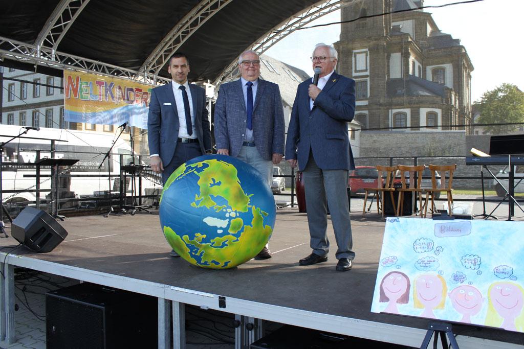 Drei Männer stehen auf der Bühne vor einem Globus.