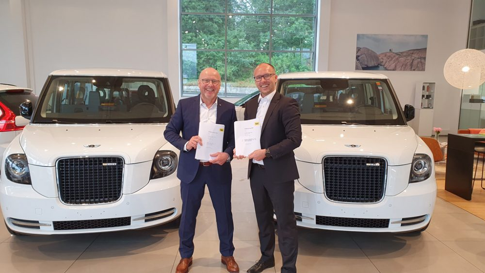Zwei Herren stehen vor zwei weißen Autos.