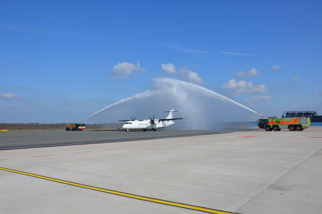 Flugzeug unter der traditionellen Wasserdusche der Flughafenfeuerwehr auf der Rollbahn.